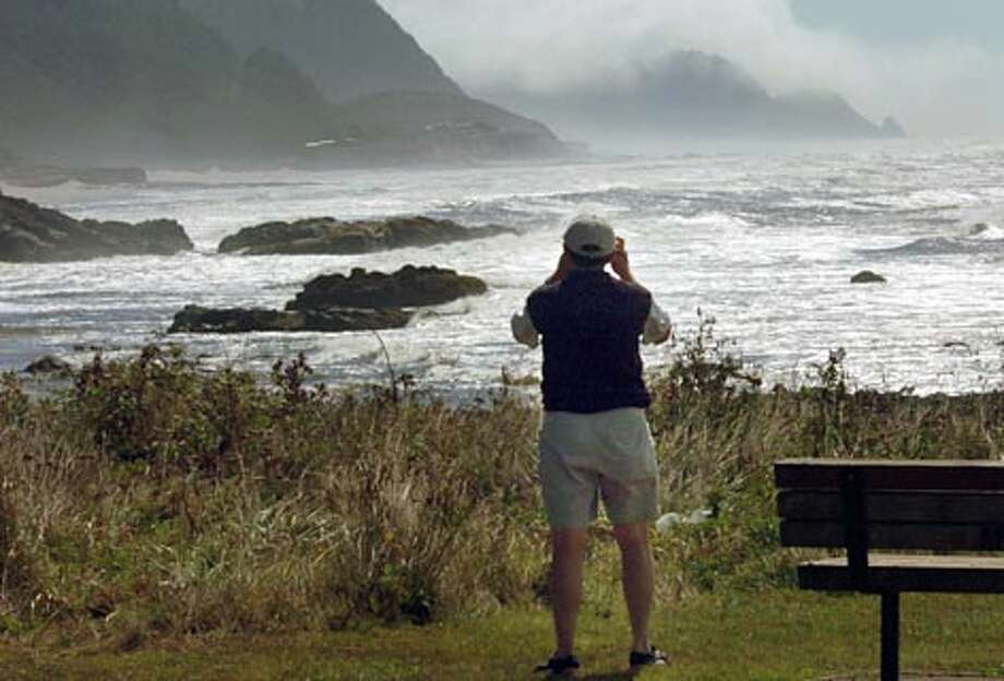 A tourist gets a good picture of the grandeur of the Oregon coast from the Bob Creek Wayside north of Florence on the Oregon coast. (Jeff Larsen / Seattle P-I)