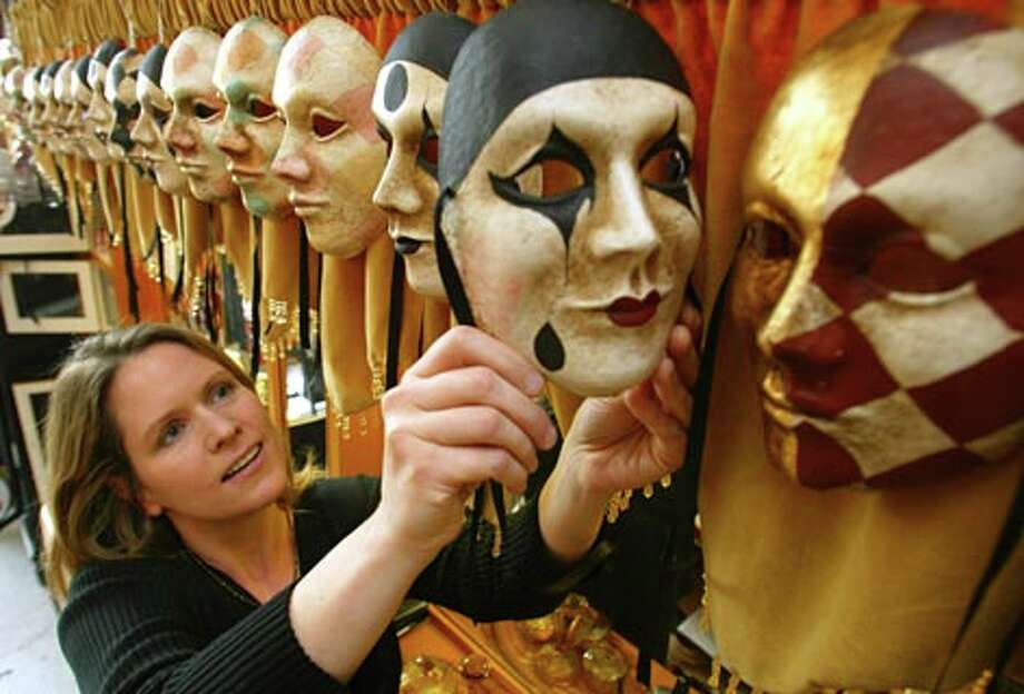 Juliet Stratton examines one of the many one of the many handmade Venetian masks they sell at Casa e Cucina Francesca on 1st Street in Snohomish. Stratton a sales person in the store. (Grant Haller / Seattle P-I)
