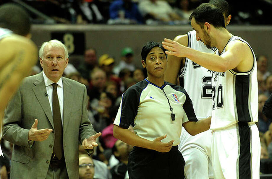 NBA official Violet Palmer listens as Manu Ginobili (20) and coach Gregg Popovich question a call at the AT&T Center on Thursday. BILLY CALZADA / gcalzada@express-news.net