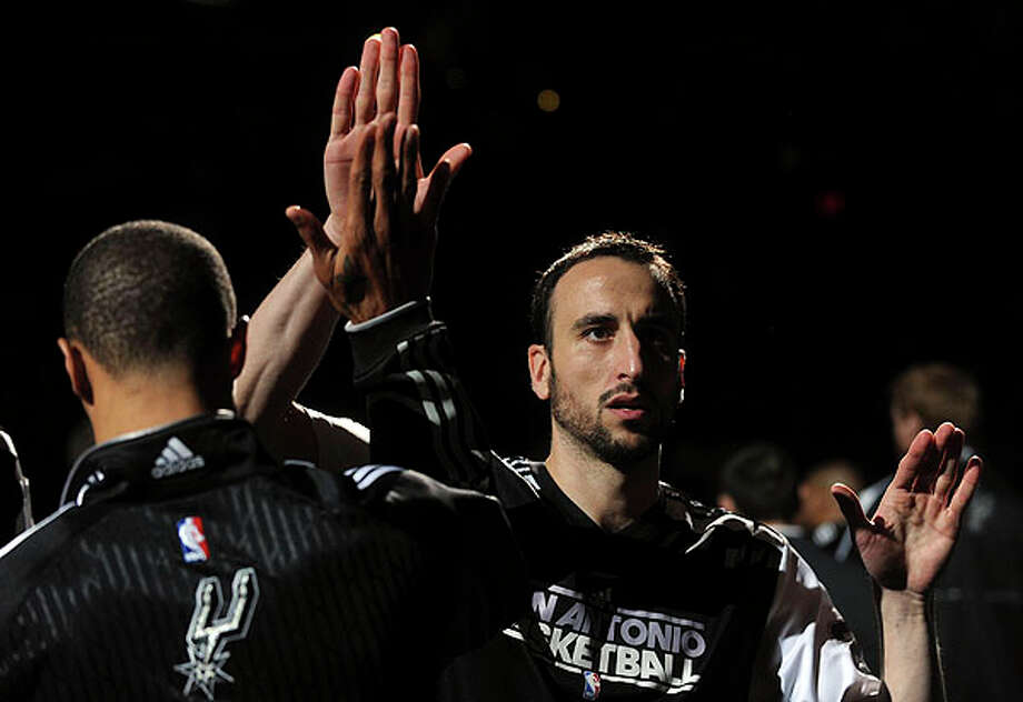 Spurs guard Manu Ginobili high-fives his teammates as he is introduced before the Celtics game at the AT&T Center on Thursday. BILLY CALZADA / gcalzada@express-news.net