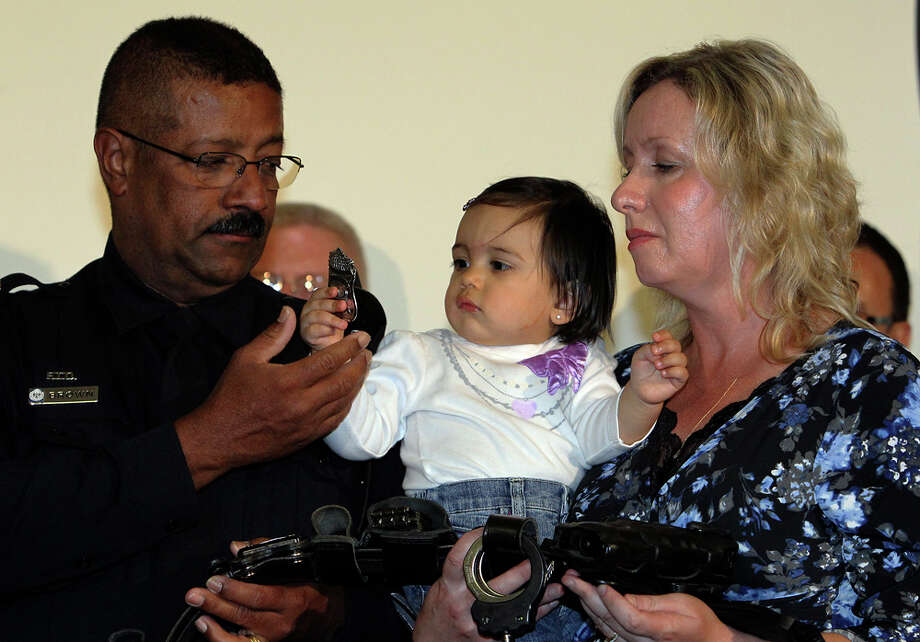 The badge worn by deceased San Antonio Police Officer Stephanie Brown is held by Brown's daughter Audrey De La Rosa as Stephanie Brown's parents, Stanley and Shawn Brown, observe. Photo: Kin Man Hui / San Antonio Express-News