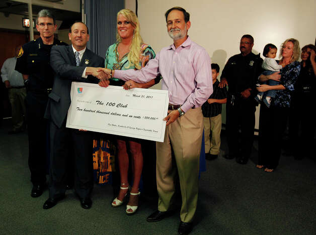 Dr. George Rapier (fourth from left) and his wife, Kym, present a check for $200,000 to 100 Club of San Antonio President Richard Miller at a press event at San Antonio Police Headquarters with Chief William McManus (left) on Mar. 31. The Rapiers gave the donation in honor of Officer Stephanie Brown, who was killed by a wrong-way driver. Brown's mother, Shawn (second from right), holding Brown's daughter, Audrey De La Rosa, and Brown's father and patrolman Stanley Brown (fourth from right) were present for the event. Photo: Kin Man Hui