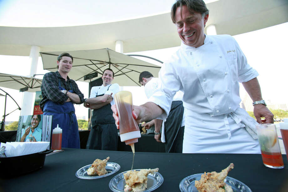 John Besh, with fellow chefs Jason Dady (left) and Steve McHugh watching, applies the finishing touch to a sample of fried quail, which he drizzled with orange blossom honey and served with Louisiana crawfish boil potato salad. Photo: Tom Reel / © 2011 San Antonio Express-News