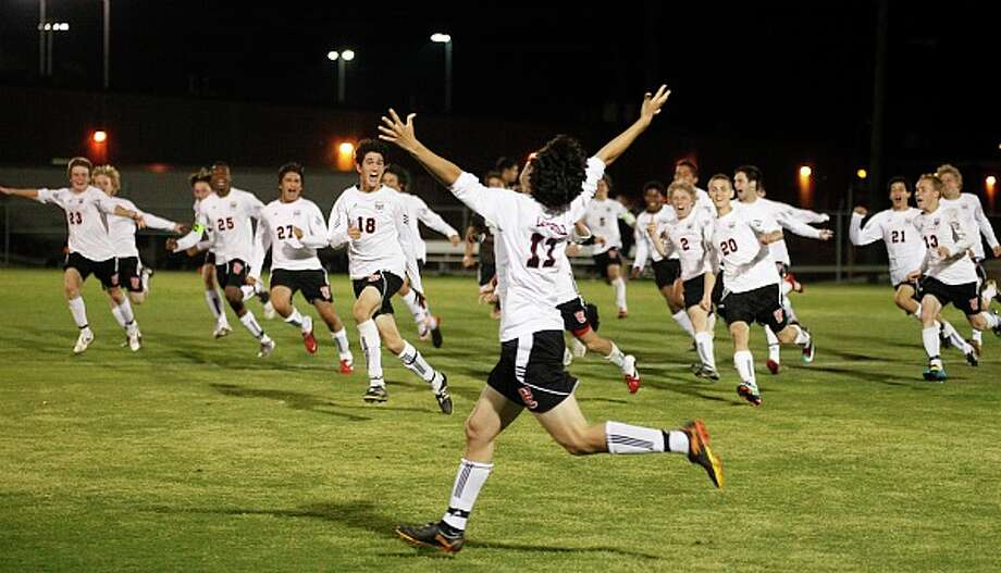 Churchill's Cristian Alcala raises his arms in celebration after his game-winning goal as teammates rush to greet him. Churchill beat Clark 4-3 in a shootout after a 1-1 tie at Blossom Stadium to reach the third round of the Class 5A playoffs. J. MICHAEL SHORT/SPECIAL TO THE EXPRESS-NEWS