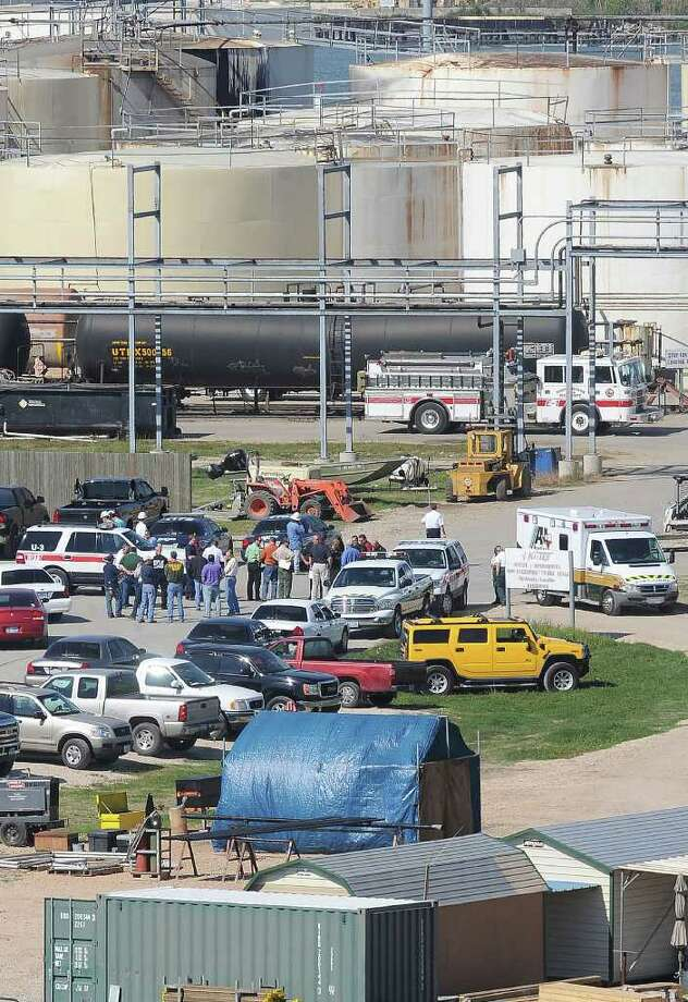 Emergency officials gather in the parking lot of KMTEX chemical facility in Port Arthur Thursday after an explosion killed one person and hospitalized two others. The facility is located next to the Intracoastal Bridge.  Guiseppe Barranco/The Enterprise / Beaumont