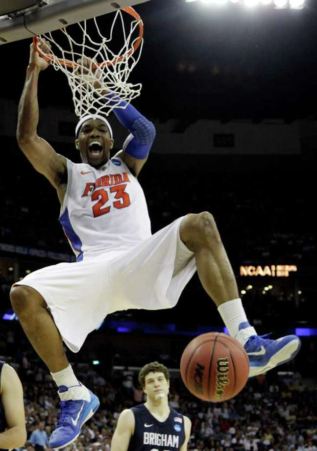 Florida's Alex Tyus (23) reacts after dunking in front of BYU's Jimmer Fredette (32) during overtime of the NCAA Southeast regional college basketball semifinal game Thursday, March 24, 2011, in New Orleans. (AP Photo/David J. Phillip) Photo: David J. Phillip