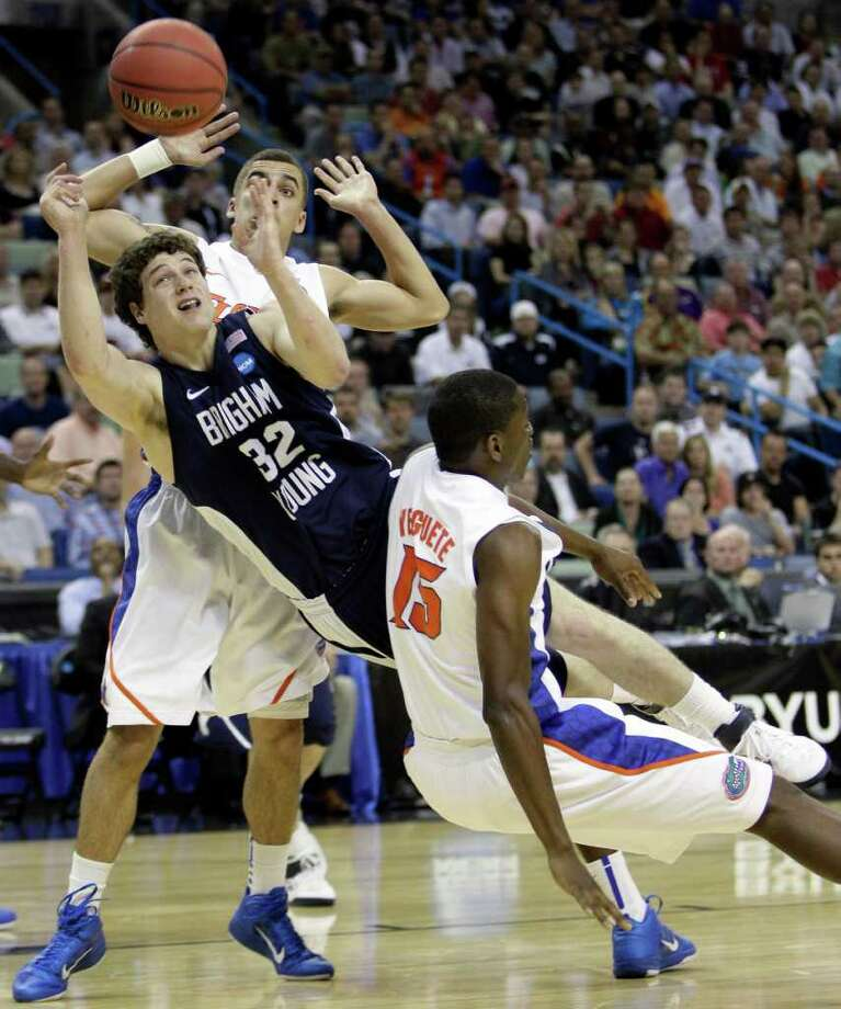 BYU's Jimmer Fredette (32) is fouled as he drives between Florida's Will Yeguete (15) and Scottie Wilbekin during the second half of the NCAA Southeast regional college basketball semifinal game Thursday, March 24, 2011, in New Orleans. (AP Photo/Patrick Semansky) Photo: Patrick Semansky