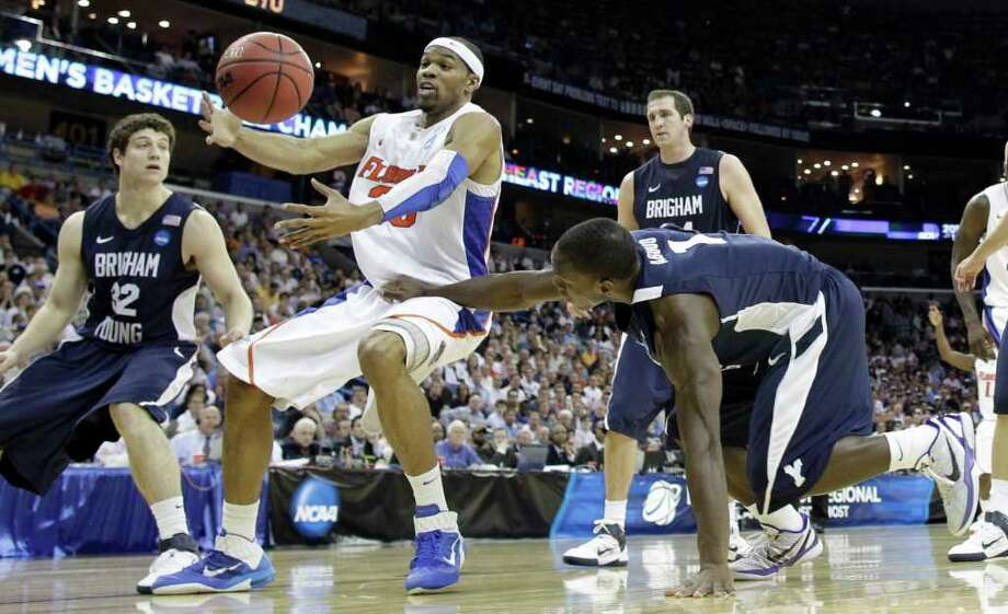 Florida's Alex Tyus (23) battles for a loose ball with BYU's Jimmer Fredette (32) and Charles Abouo (1) during the second half of the NCAA Southeast regional college basketball semifinal game Thursday, March 24, 2011, in New Orleans. (AP Photo/David J. Phillip) Photo: David J. Phillip
