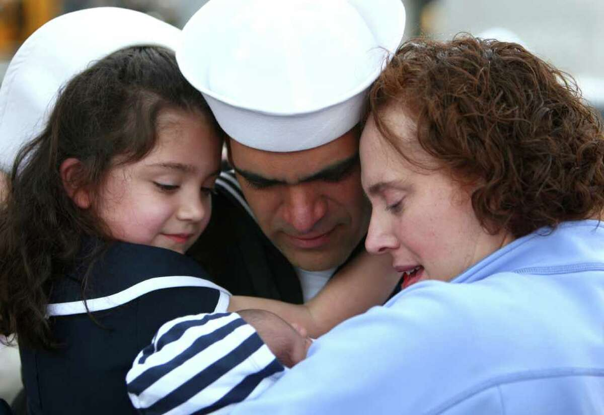 Nisse Fonseca, center, meets his three week-old son Cuper for the first time as he is greeted by his wife Sarah and daughter Laura, 5, after he disembarked the U.S.S. Abraham Lincoln during the aircraft carrier's return to its home port on Thursday at Naval Station Everett. The aircraft carrier was on a six month deployment.