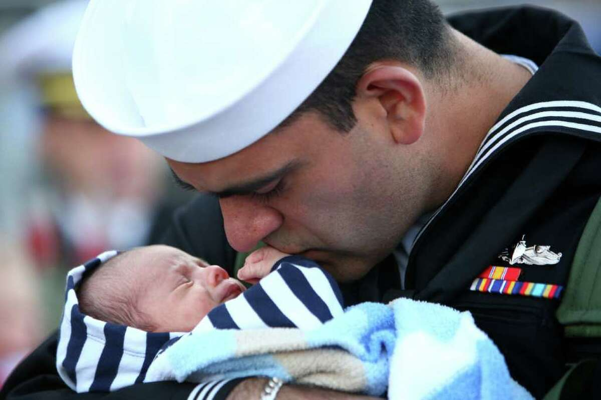 Nisse Fonseca meets his three week-old son Cuper for the first time as he is greeted his family after he disembarked the U.S.S. Abraham Lincoln during the aircraft carrier's return to its home port on Thursday at Naval Station Everett. The aircraft carrier was on a six month deployment.