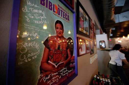 A poster signed by author Sandra Cisneros hangs in Tommy Moore's Cafe & Deli in District 2 on the East Side. New census data shows an increase in the Hispanic population in a district which was once majority African-American. Photo: Kin Man Hui/kmhui@express-news.net / San Antonio Express-News