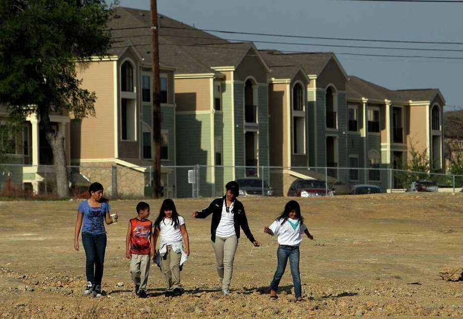 Kids living in the Sutton Oaks apartments in District 2 on the city's East Side walk toward Woodard Community Center near Walters Street on Mar. 30. Latest census data shown an increase in the Hispanic population in District 2, which was once a majority African-American district. Photo: Kin Man Hui/kmhui@express-news.net / San Antonio Express-News