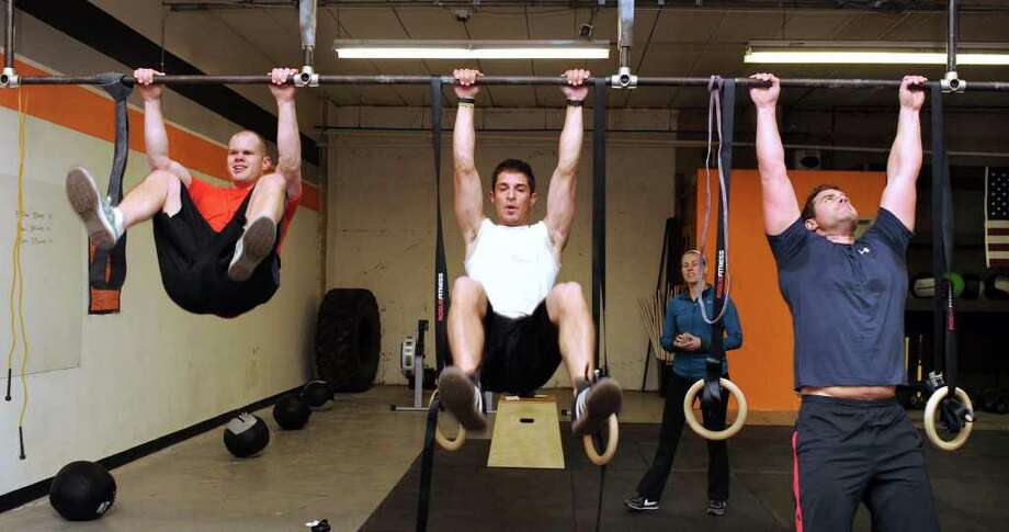 From left to right are Matt Duplessis, Ian Sieller and Matt Lubrano doing a Cross Fit WOD (workout of the day), at Cross Fit 203, in Danbury. Photo taken Thursday, March 31, 2011. Photo: Carol Kaliff / The News-Times