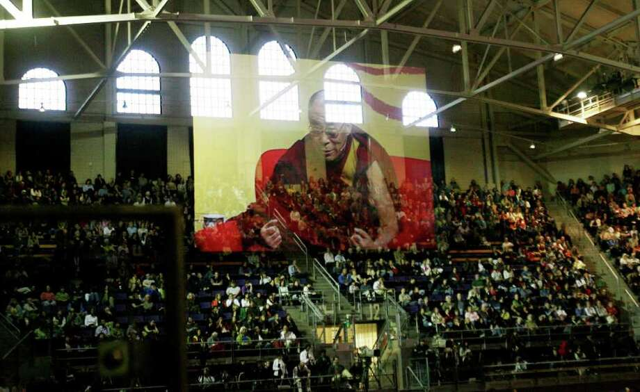 The image of The Dalai Lama, reflected in a glass panel,  appears suspended in air as he speaks at Hec Ed Pavilion in Seattle on Friday, April 11, 2008. (Seattle Post-Intelligencer/Dan DeLong)  COMMENTS: I liked how the The Dalai Lama appears floating above his adoring Seattle audience. Photo: Seattle Post-Intelligencer