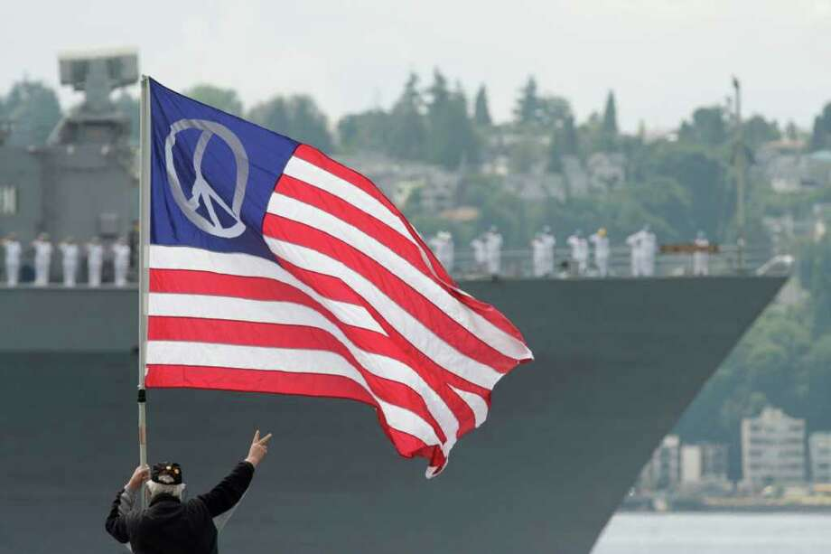 "Richard Newton displays the peace sign as the USS Germantown passes the Seattle waterfront  on Wednesday, July 30, 2008. ""I'm stating my opinion. We need to have a more peaceful approach to things,"" Newton said. The naval ship joined the USS Princeton and other vessels for the Parade of Ships at Elliott Bay, marking the beginning of Seafair's Fleet Week. (Seattle Post-Intelligencer/Dan DeLong)