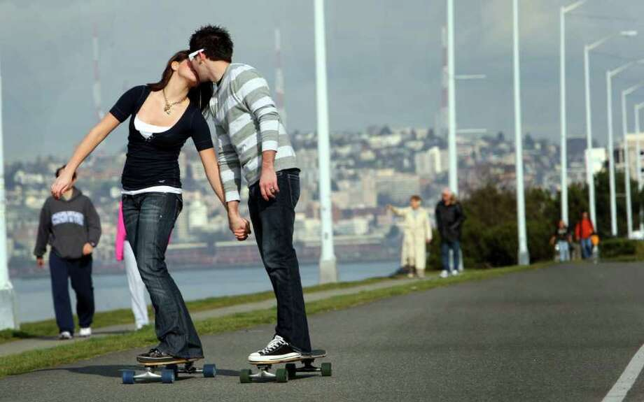 "Angie Sherbina, 16, and her boyfriend Rod Lats,19, both from Federal Way, WAsh., skateboard along Alki Beach on Harbor Ave. and Alki Ave. SW on Valentines Day on February 14, 2008.  ""After this I'm going to surprise her with something."" said Rod ""and then take her out to dinner.""  The couple spent the ""whole day hanging out together"".  ""Being together on a sunny day is just great."" said Rod. (Photo/Seattle Post-Intelligencer/Karen Ducey)