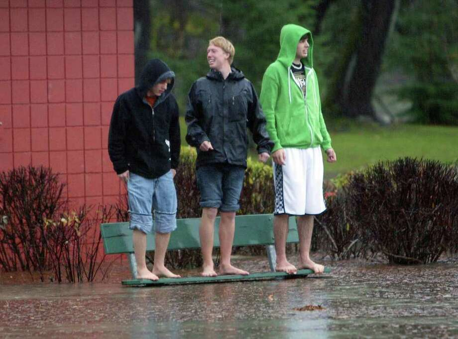 From left to right: Codey Schneider, 17, Matthew Lynne, 17, and Doug Devin-Aberle, 17, all from Snoqualmie, Wash. observe the rising river from the top of a bench in a park in Snoqualmie, Wash. on November 12, 2008.  Severe flooding is expected due to the weather. (Karen Ducey/Seattle Post-Intelligencer)