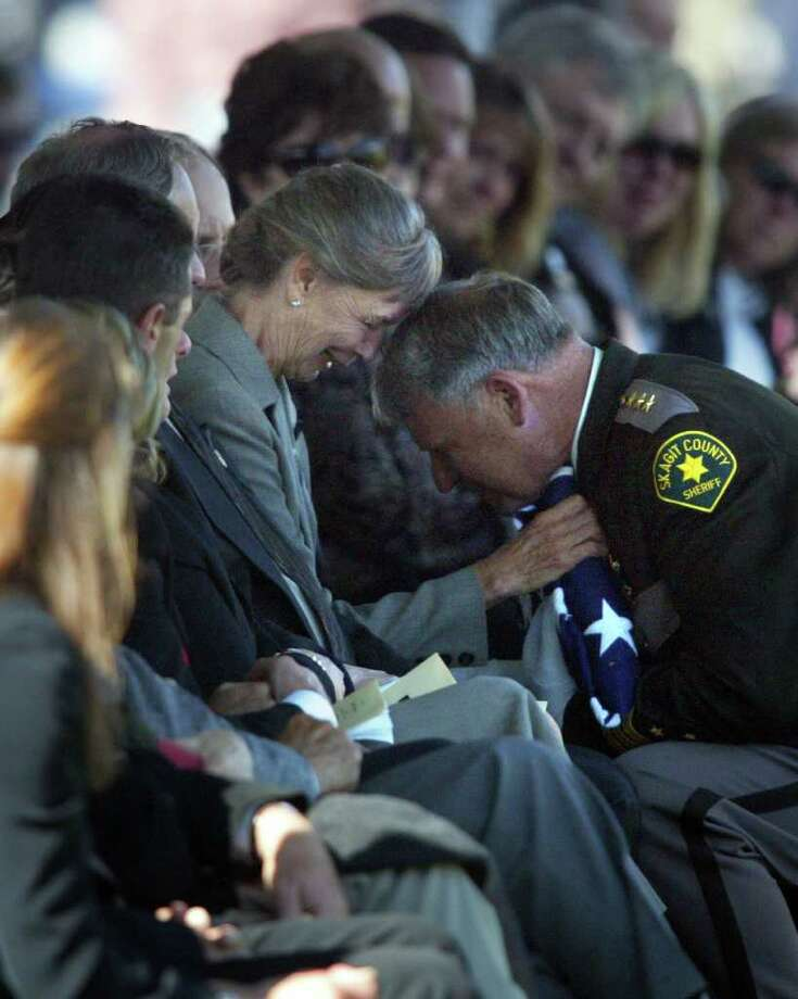 Skagit County Sheriff Rick Grimstead hands a flag over to Deputy Anne Jackson's mother during her memorial service. A memorial service was held at the Burlington-Edison HS in Burlington, Wash. for Deputy Anne Jackson on September 9, 2008. Jackson was killed in the line of suty along with five others last week during a killer's rampage in Sedro-Wooley, Wash.(photo/Karen Ducey/Seattle PI) Photo: Karen Ducey, The Seattle Post-Intelligencer
