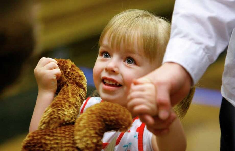 Zada Smith, 2, greets the Mariners Moose during a reception held after her adoption in Seattle November 14, 2008. As part of National Adoption Day, 22 area foster kids were formerly adopted. Zada and her twin brother, Zach, were formally adopted by Callie Starks and her family. 