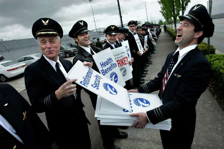 1st Officer Brian Moynihan, right, reacts as Cpt. Claude Tirman jokes about his preference for a sign addressing retirement security during an informational picket of approximately 300 Alaska Airlines pilots outside the Alaska Air Group shareholders meeting at the Museum of Flight Tuesday, May 20, 2008. Tirman plans to retire on Nov. 30. The pilots were gathered to draw attention to their ongoing contract negotions. (Seattle Post-Intelligencer/Andy Rogers)  There were a huge number of pilots at this picket, and I spent a lot of time trying to show as many of them as possible in my photo. In the end, the personality that shows through in a humorous exchange between these men ended up being far more interesting to me...and you still get to see a lot of pilots lined up. Photo: ANDY ROGERS, SEATTLE POST-INTELLIGENCER / SEATTLE POST-INTELLIGENCER