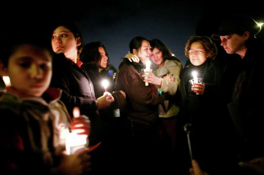 Karina Blanco Lopez, 15, (center right) and her aunt Rosalba Naranjo (center left) - gather in front of the home where Noemi Lopez, Karina's mother, was found stabbed to death.  Noemi's ex-husband and Karina's father, Jose Angel Blanco, was charged with first-degree murder in the domestic violence slaying of his ex wife and likely fled to Mexico.  Photographed on December 2, 2008 in Seattle.  (Photo/Seattle Post-Intelligencer/Joshua Trujillo)