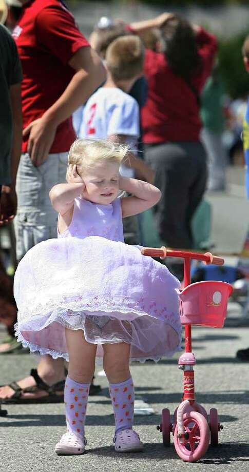 Three-year-old Vivian Gaither, of Seattle, didn't seem too impressed as the wind blew her dress up, as she and her family watched stunt planes perform at Seafair.