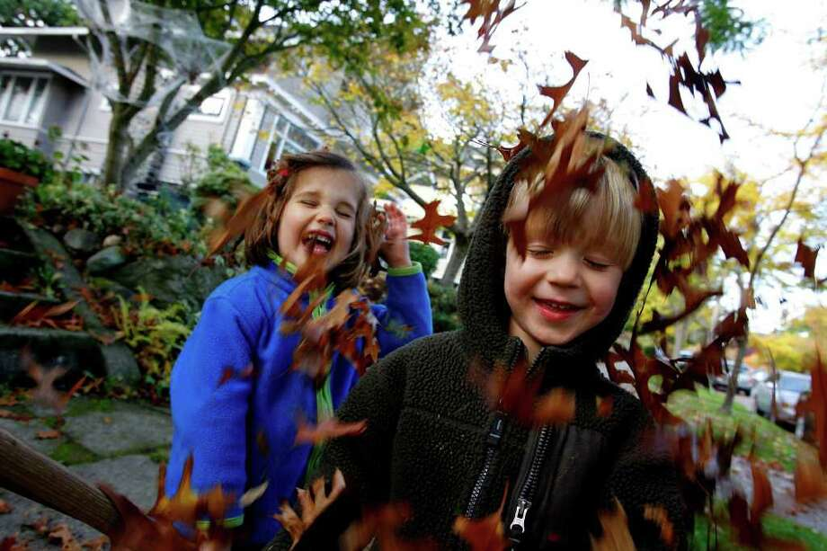 Mea Shelton, left, andTate Ranson giggle with delight as Mea's mother pours autumn leaves over their heads in Seattle's Mount Baker neighborhood on October 21, 2008.