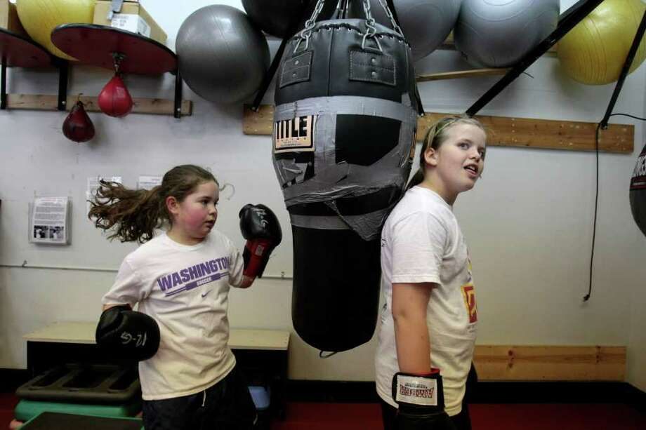 In my life, I have never seen young girls boxing. I like the mixture of pure youth and the rough sport.   Rachael Carrell, left, punches the bag as Shannon McRae holds it still, during boxing class at Cappy's gym on April 29, 2008. Electives such a yoga, taekwondo, dance and boxing fill the gym requirement at Lake Washington Girls Middle School. Seattle P-I photo/Meryl Schenker Photo: Meryl Schenker / Seattle Post-Intelligencer