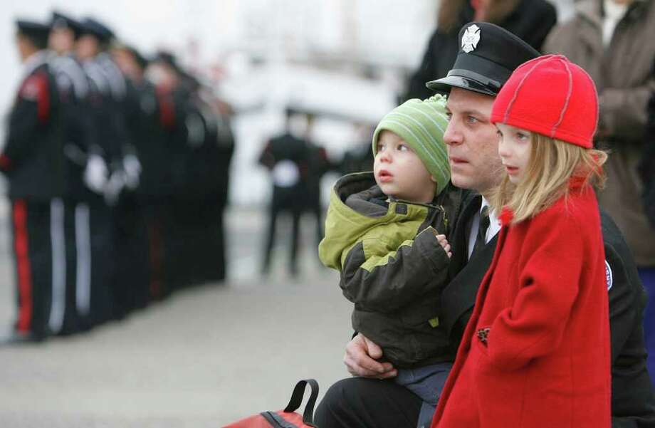 Seattle firefighter Kevin McSherry watches with his daughter Maddie and his son Jack as the funeral procession to honor battalion chief James H. Scragg passes by on Friday February 8, 2008. 