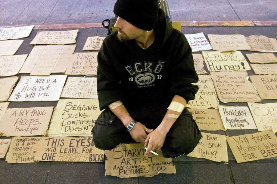 Bruce Daniels sits by a mosaic of signs he created along with Marji King, not shown,  in front of the downtown Seattle Nordstrom on October 12, 2008. Their creation has drawn a lot of eyes and money to help keep them fed while on the streets.