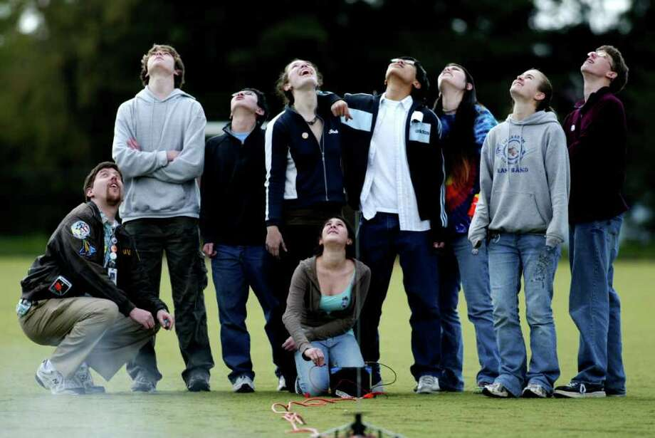 Watching the parachut pop out of their rocket are, from the left: Peter Schurke, teacher; Nat Mote, 15, soph; Patrick Ma, 16, soph; Sarah Crane, 16, Jr; Alex Kon, 16, Jr; Nelly Nicklason, 17, Jr; Kim Smith, 17, Jr; Julian Picard, , 16, Jr; and Katy Loubet-Senear, 17, Jr, kneeling, who fired the rocket. Ingraham High School rockety team launches a rocket at school. The Ingraham High School rocketry team has qualified for the national finals of the Team America Rocketry Challenge  in Virginia in mid-My. They're the only team in Washington state to qualify this year.  They've desinged, built and tested a model rocket that can fly for close to 45 seconds and as high as 750 feet, while carying two raw eggs -- and then parachute back to the ground unbroken.  The top 10 teams will share a prise pool of $60,000.  Friday, Apri 25, 2008. Seattle Photo: Grant M. Haller, Seattle Post-Intelligencer / Seattle Post-Intelligencer