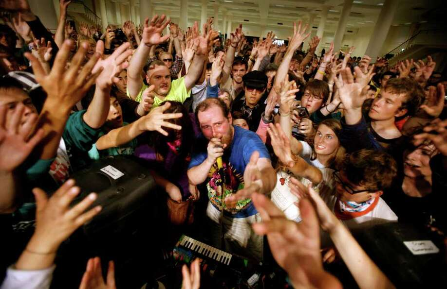 Audience members surround Dan Deacon as he performs his energetic electronic music at Bumbershoot