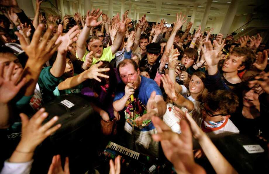 Audience members surround Dan Deacon as he performs his energetic electronic music at Bumbershoot, Seattle's Labor Day weekend arts festival. Sept. 1 