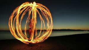 "In this ten second exposure Sarah Johnson, of Seattle, spins a cage-like ball of fire as she practices her art at Richmond Beach in Shoreline near Seattle Tuesday March 4, 2008. ""Fire has always been a fascination for me,""  Johnson recalled.  ""I was that kid at the campfire lighting twigs...and watching them burn.""  (Seattle Post-Intelligencer/Mike Urban)   The photo is basically a double exposure. The first exposure is a flash on Sarah's face. I set up a strobe unit off to Sarah's right and triggered it with a radio transceiver. After a few practice timing runs we lit her torch. The torch is essentially a wad of fuel soaked rags hooked to a length of chain with a handle. As she twirled the torch, the ten-second open shutter captured the travel of the fire."