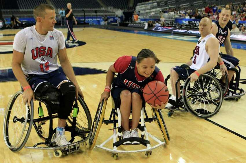 U.S. Wheelchair basketball player Patty Cisneros, of Denver, grabs a rebound with Jeff Glassbrenner, left, in on the play during an exhibition at the Final Four at Reliant Stadium Friday, April 1, 2011, in Houston. ( Brett Coomer / Houston Chronicle )