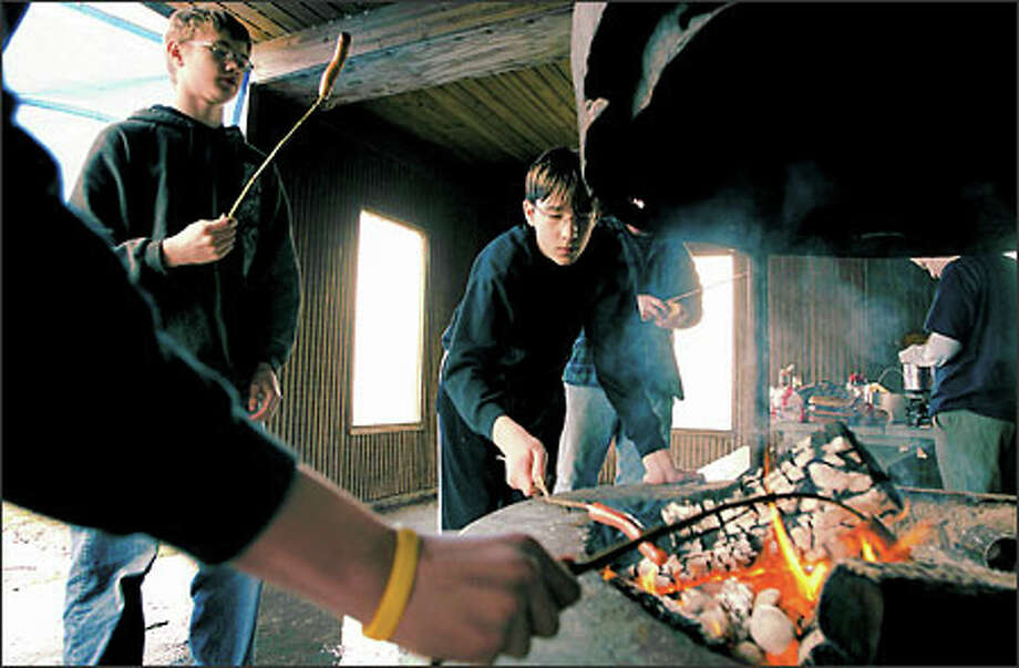 Campers Andrew Johnson, 15, left, and Alex VanDenEnde, 14, roast hot dogs in a Blake Island State Park shelter. The boys participated in a weekend outing with Venturing Crew 284, a division of the Boy Scouts. (Meryl Schenker / Seattle P-I)