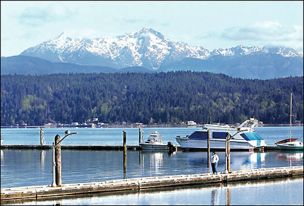 A woman takes an early-morning stroll on the Alderbrook resort pier on the shores of Hood Canal. The Olympic Mountains are in the background. (Jeff Larsen / Seattle P-I)
