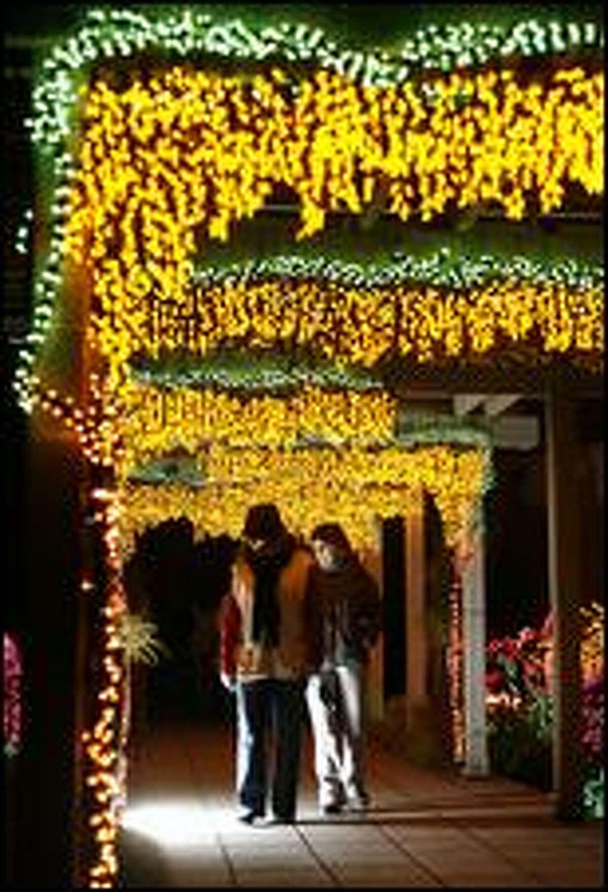 "Visitors stroll beneath trellises covered in lights at ""Garden d'Lights"" at the Bellevue Botanical Gardens in Bellevue Dec. 4, 2008. (Mike Urban / Seattle P-I)"
