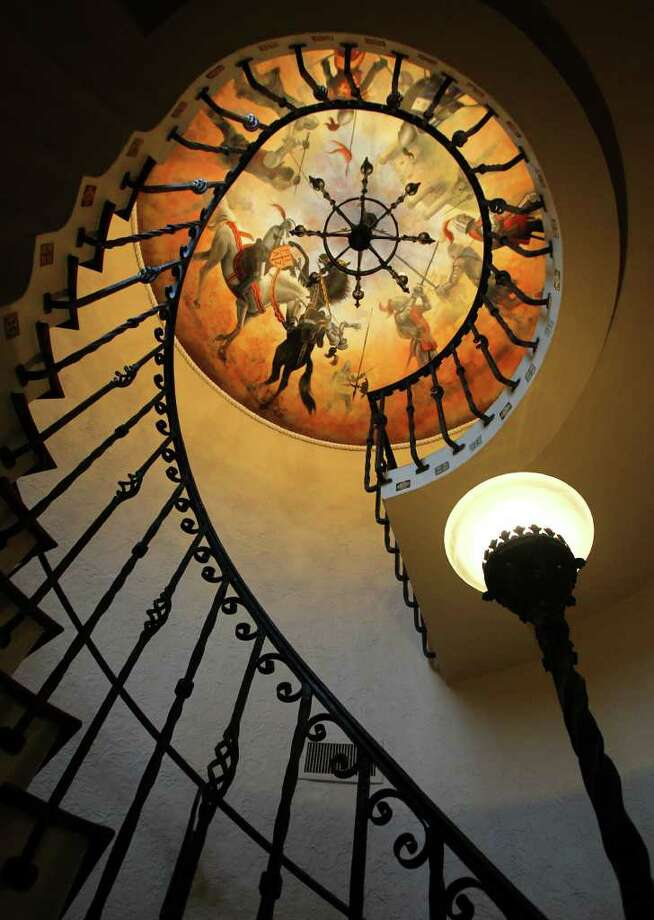 A beautiful spiral staircase is topped by a painted domed ceiling. The stairwell is accented with ornate iron work serving as a hand rail. Photo: JOHN DAVENPORT/jdavenport@express-news.net