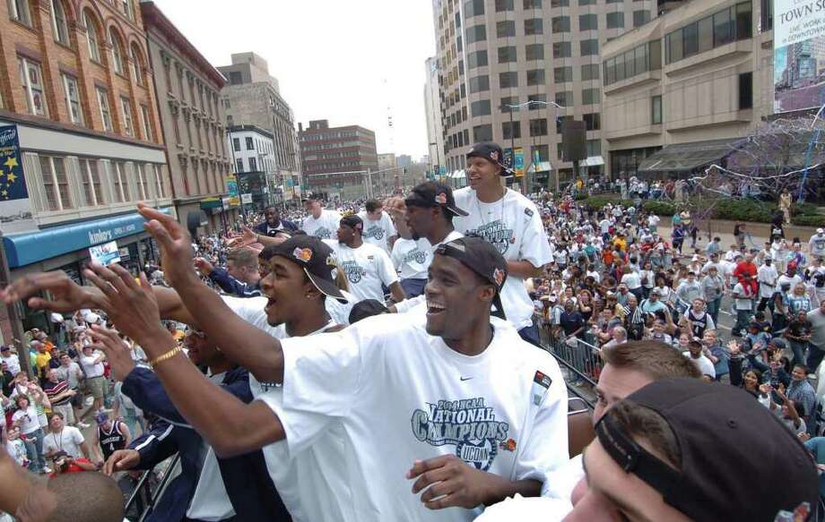Emeka Okafor waves to the crowd with his University of Connecticut men's basketball teammates as they pass outside the Hartford Civic Center during the team's national championship parade in 2004. The Huskies can win their third national championship at Reliant Stadium in Houston with two more victories. Photo: File Photo / The News-Times File Photo