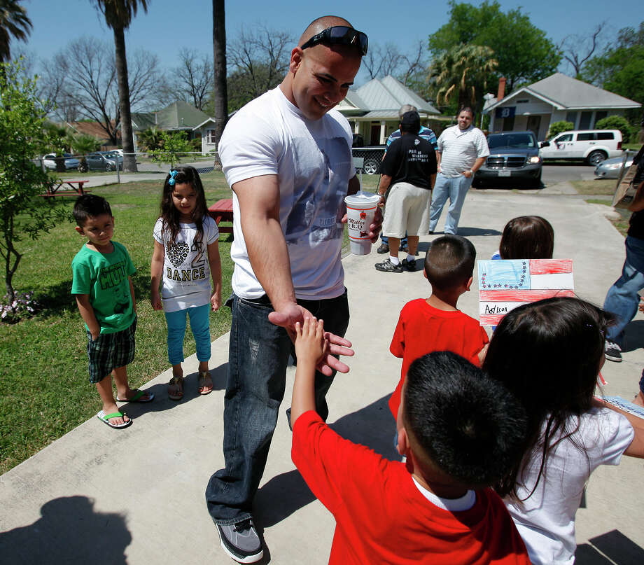 Marine Staff Sgt. Dominic Fernandez greets young guests upon his arrival at his grandparents home on Friday. Fernandez was injured and lost the lower section of his right leg while serving in Afghanistan in July 2010 when he stepped on a hidden ground pressure plate explosive. Fernandez was welcomed home by numerous aunts and uncles at the home of his grandparents Edward and Genevieve Sanchez. Fernandez, 32, is a graduate of Edison High School. Photo: Kin Man Hui/kmhui@express-news.net / San Antonio Express-News