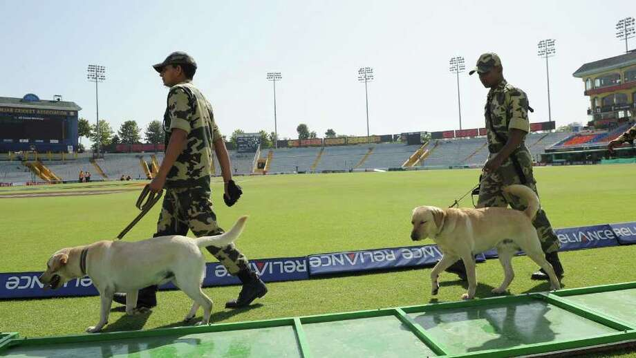 Central Reserve Police Force (CRPF) bomb-squad officials search the empty stadium with a sniffer dogs prior to the start of the ICC World Cricket Cup 2011 second semi-final match between India and Pakistan at The Punjab Cricket Associaton (PCA) Stadium in Mohali on March 30, 2011. Cricket-crazy India and Pakistan head into an epic World Cup showdown that will showcase the bitter rivalry and common bonds between the estranged nuclear-armed neighbours. The teams clash in the semi-final of the competition with the winner facing Sri Lanka in the World Cup final in Mumbai on April 2. AFP PHOTO/Indranil MUKHERJEE Photo: INDRANIL MUKHERJEE, AFP/Getty Images / 2011 AFP