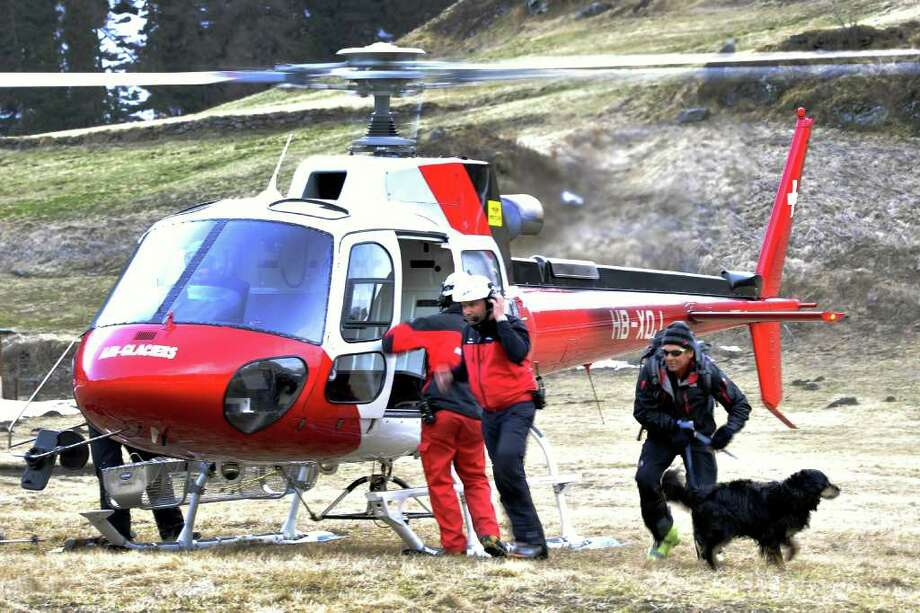 A rescuer with his dog leaves a helicopter in the village of Bourg-Saint-Pierre on March 26, 20110. Rescuers in the Swiss Alps found six of seven skiers missing after they were swept away by an avalanche, police in southwestern Switzerland said.There was no immediate word on their condition.They were part of a group of 11 high-altitude ski hikers caught in an avalanche near Bourg-St-Pierre, said Jean-Marie Bornet, a spokesman for police in the Swiss canton of Valais.   AFP PHOTO / FABRICE COFFRINI Photo: FABRICE COFFRINI, AFP/Getty Images / 2011 AFP