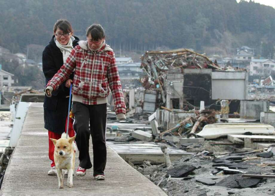 Young women walk their dog past damaged houses following the huge earthquake and tsunami waves in Minamisanriku, Miyagi prefecture on March 26, 2011.  Two weeks after a giant earthquake hit and sent a massive tsunami crashing into the Pacific coast, the death toll from Japan's worst post-war disaster topped 10,000 and there was scant hope for 17,500 others still missing.    AFP PHOTO / JIJI PRESS Photo: STR, AFP/Getty Images / 2011 AFP