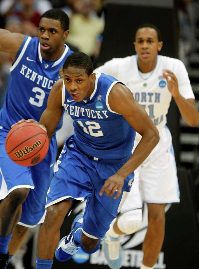 Kentucky's Brandon Knight (12) brings the ball up as teammate Terrence Jones, left, and North Carolina's John Henson, right, trail during the first half of the final of the NCAA men's college basketball tournament East regional, Sunday, March 27, 2011, in Newark, N.J. (AP Photo/Julio Cortez) Photo: AP