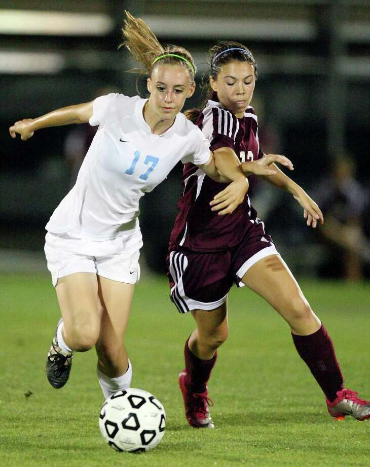 Johnson's Courtney Kukes and  Marshall's Cora Barrera struggle for position during second half action Friday April 1, 2011 at Blossom Soccer Stadium. Johnson won 3-0.   (PHOTO BY EDWARD A. ORNELAS/eaornelas@express-news.net) / SAN ANTONIO EXPRESS-NEWS (NFS)
