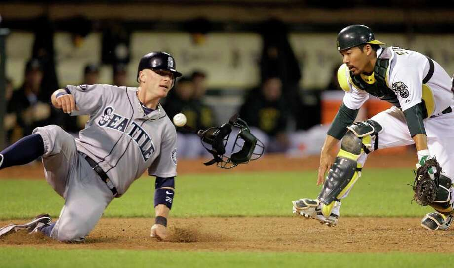 Seattle Mariners' Brendan Ryan, left, slides safe to score past Oakland Athletics catcher Kurt Suzuki during the sixth inning of a baseball game Friday, April 1, 2011, in Oakland, Calif. Ryan scored on a single by Ichiro Suzuki. Photo: AP