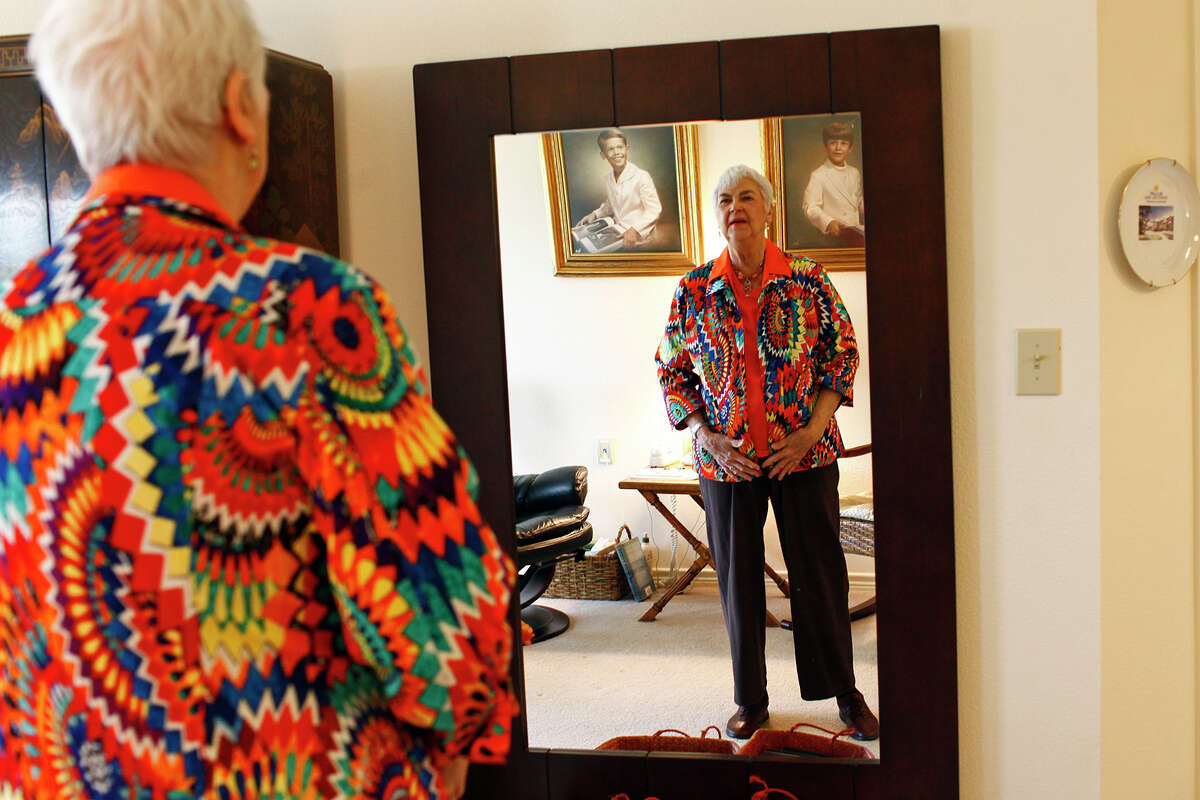 Adele Jones, 83, tries on a jacket that she plans to wear to dinner after today's ceremony in Florida.