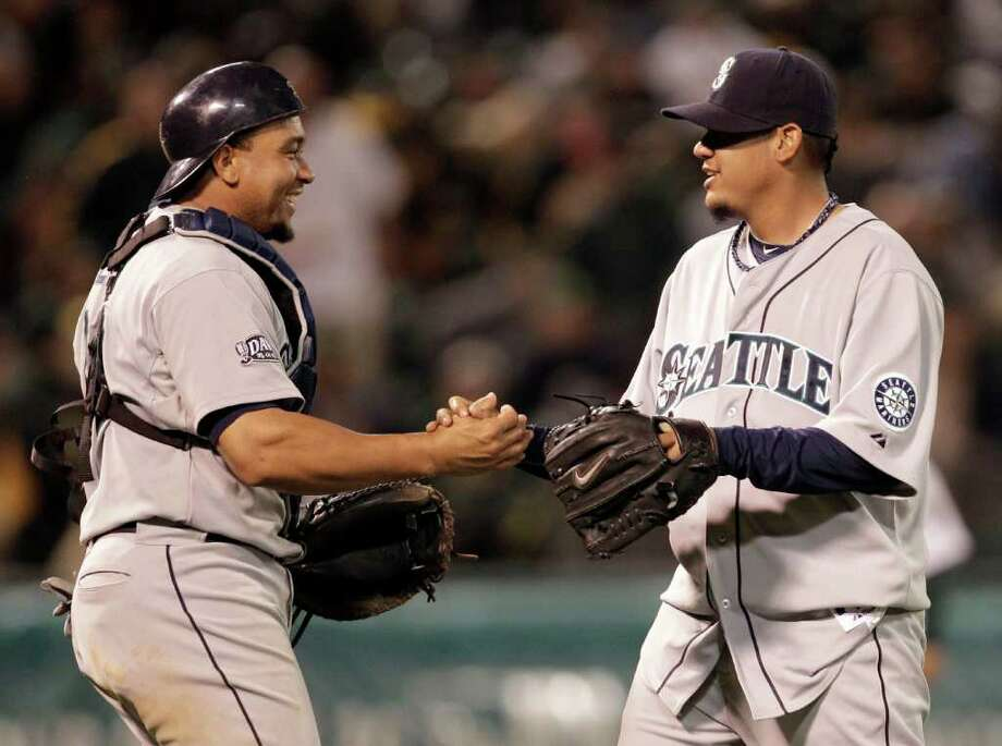Seattle Mariners' Felix Hernandez, right, is congratulated by catcher Miguel Olivo after the the 6-2 defeat of the Oakland Athletics after a baseball game Friday, April 1, 2011, in Oakland, Calif. Photo: AP