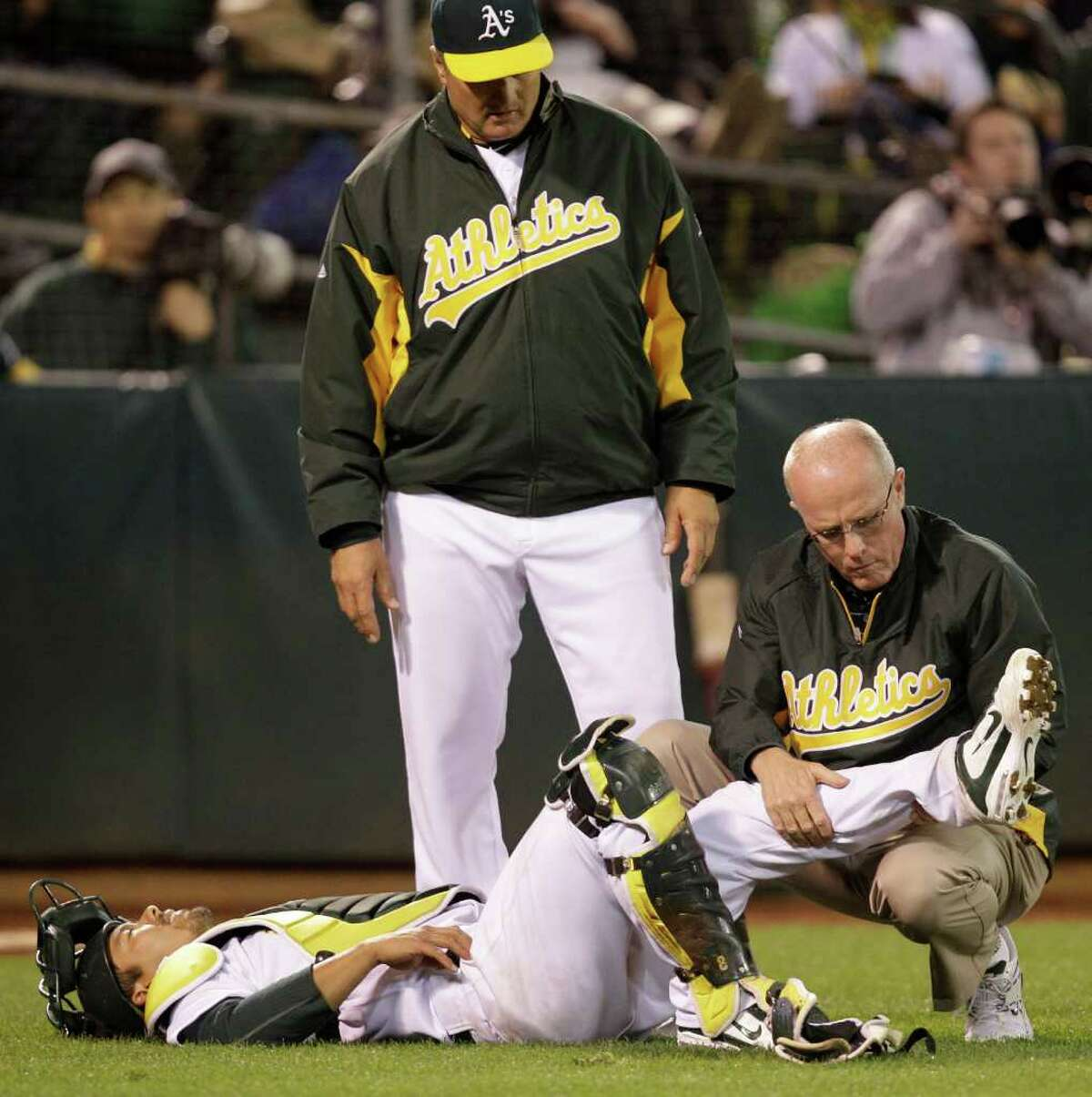 Oakland Athletics catcher Kurt Suzuki has his leg examined by assistant trainer Walt Horn during the seventh inning of a baseball game against the Seattle Mariners Friday, April 1, 2011, in Oakland, Calif.